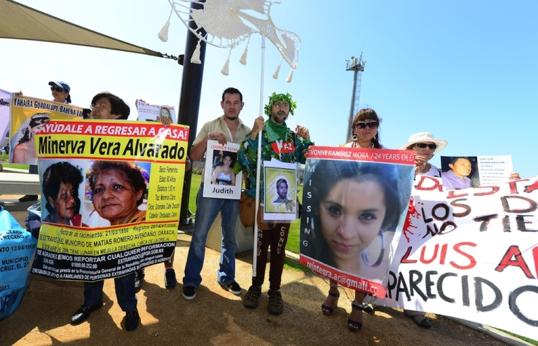 <p>People display images of dead or missing loved ones at Border Field State Park, which separates the cities of San Diego and Tijuana, on August 12, 2012 in San Diego, California, at the launch of the