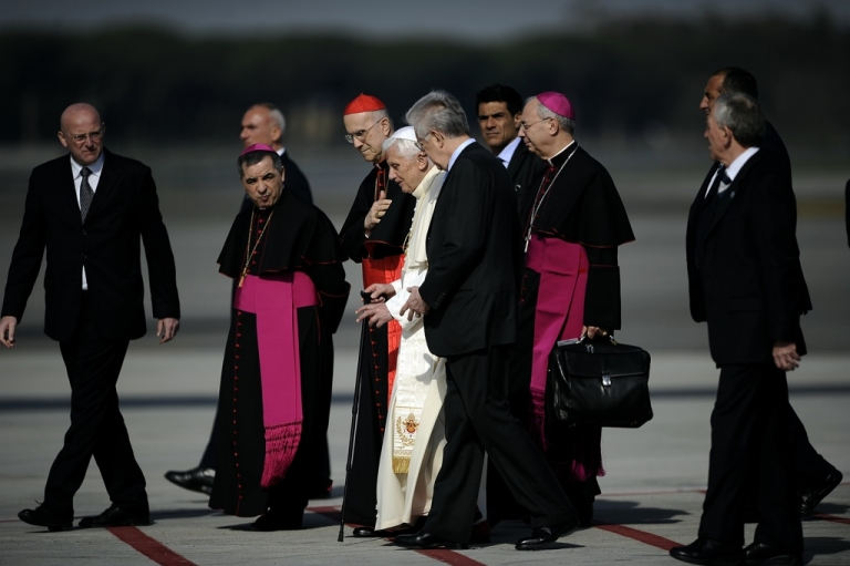 <p>Pope Benedict XVI, flanked by Vatican secretary of state Cardinal Tarcisio Bertone (L) and Italian Premier Mario Monti walks with a stick on the tarmac as he boards a plane on his way to Mexico and Cuba on March 23, 2012 at Rome's Fiumicino airport.</p>
