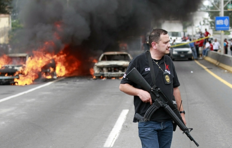 <p>A policeman stands guard near burning cars on a highway in Guadalajara, the capital of Jalisco state, Mexico, on August 25, 2012.</p>