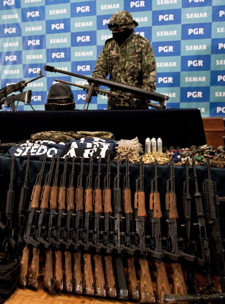 <p>A member of the Mexican Navy stands next to guns seized in the arrest of Raul Hernandez Lechuga (not in frame) -- an alleged member of the drugs cartel 'Los Zetas' -- displayed during a presentation to the news media in Mexico City on Dec 13.</p>