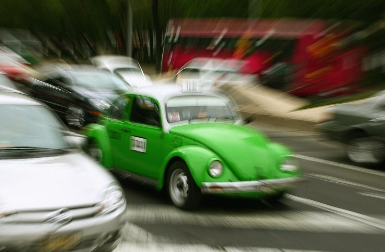 <p>A taxi driver takes his vintage beetle Volkswagen along the streets of Mexico City in 2007.</p>