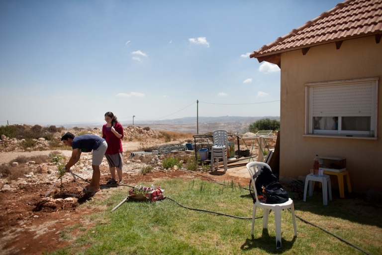 <p>Jewish settlers water a tree at the West Bank settlement outpost of Migron on August 28 in Migron. In accordance with Israel's High Court ruling, Migron must be vacated within the next few days, but deadlines continue to be pushed back.</p>