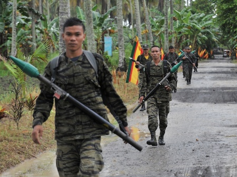 <p>Moro Islamic Liberation Front (MILF) rebels in the Philippines patrol inside their base at Camp Darapan in the southern Philippines.</p>