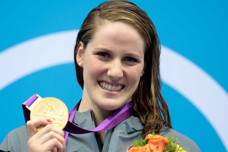 <p>Missy Franklin of the United States celebrates with her gold medal during the medal ceremony for the Women's 100m Backstroke on Day 3 of the London 2012 Olympic Games at the Aquatics Centre on July 30, 2012 in London, England.</p>