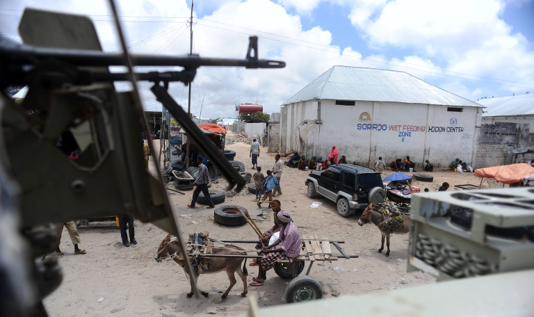 <p>People go about their daily lives as Ugandan African Union peacekeepers patrol the outskirts of Mogadishu on Sept. 12, 2012. Somalia's president survived an assassination bid that day, just two days into his new job, when bomb blasts claimed by Islamist rebels rocked the Mogadishu hotel where he was meeting Kenya's foreign minister. Another bomb attack struck Mogadishu on Sept. 20, 2012, killing at least 15 people.</p>