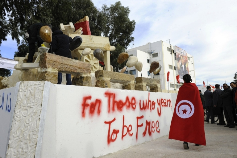 <p>A person caped in the Tunisian flag walks past a statue representing the cart of Mohamed Al Bouazizi, the fruit vendor whose self-immolation sparked the revolution that ousted a dictator and ignited the Arab Spring, on Dec. 17, 2011 in Sidi Bouzid. Thousands of Tunisians rallied in celebration of the first anniversary of the popular uprising that toppled their long-standing dictator and unleashed the Arab Spring revolutions.</p>