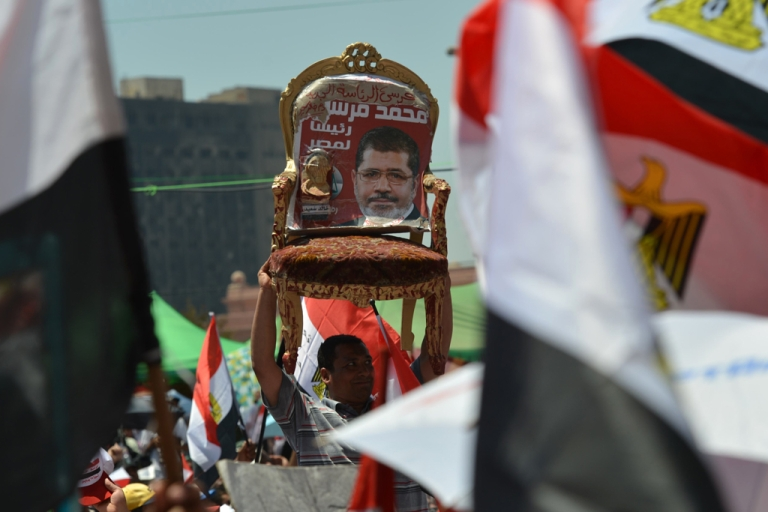 <p>An Egyptian man holds a chair with a portrait of president-elect Mohamed Morsi, as others wave their national flags, during a rally in Tahrir Square in Cairo on June 29, 2012 as crowds of Egyptians wait to hear Morsi address his supporters on the eve of his swearing-in as Egypt's first civilian president.</p>