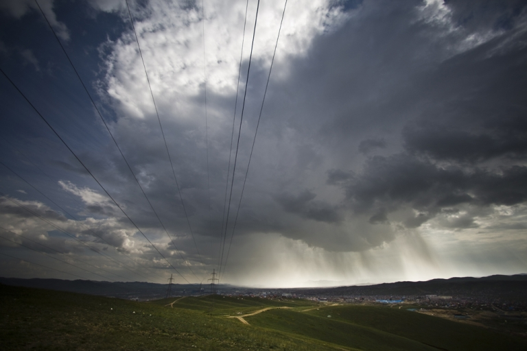 <p>Power lines and menacing storm clouds hover over Ulan Bator's ger district. The district is home to over half of the capital city's population.</p>