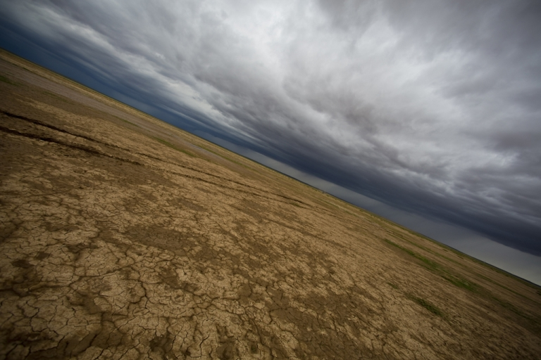 <p>Storm clouds and a desertified landscape are seen into the horizon in Mongolia's Gobi Desert.</p>