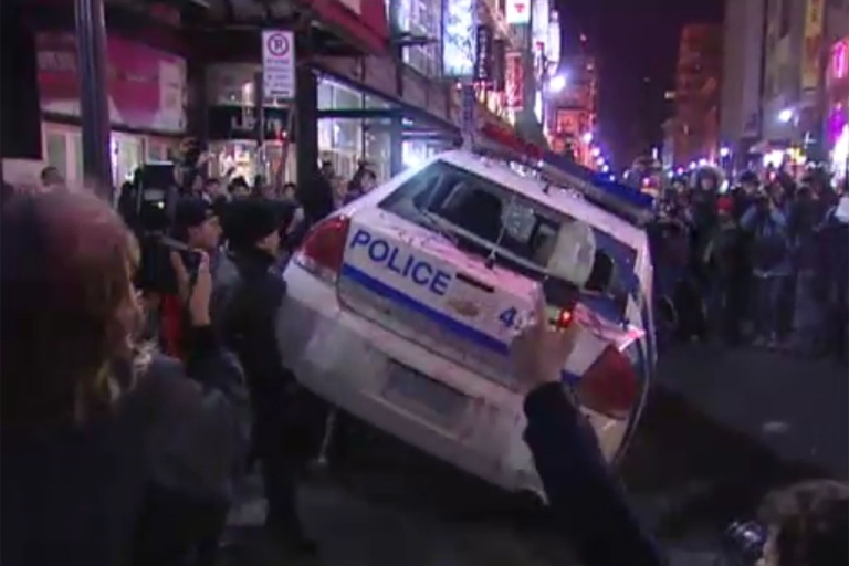 <p>Activists overturn a police cruiser during demonstrations in Montreal on Thursday. About 150 were arrested in the 15th annual anti-police brutality march.</p>