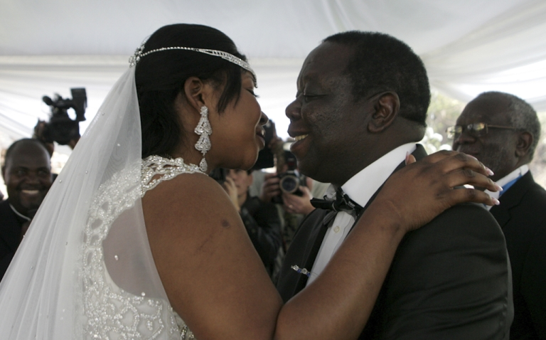 <p>Zimbabwe Prime Minister Morgan Tsvangirai (R) kisses his wife Elizabeth Macheka (L) after exchanging vows at a customary law ceremony during their wedding held in Harare on September 15, 2012.</p>