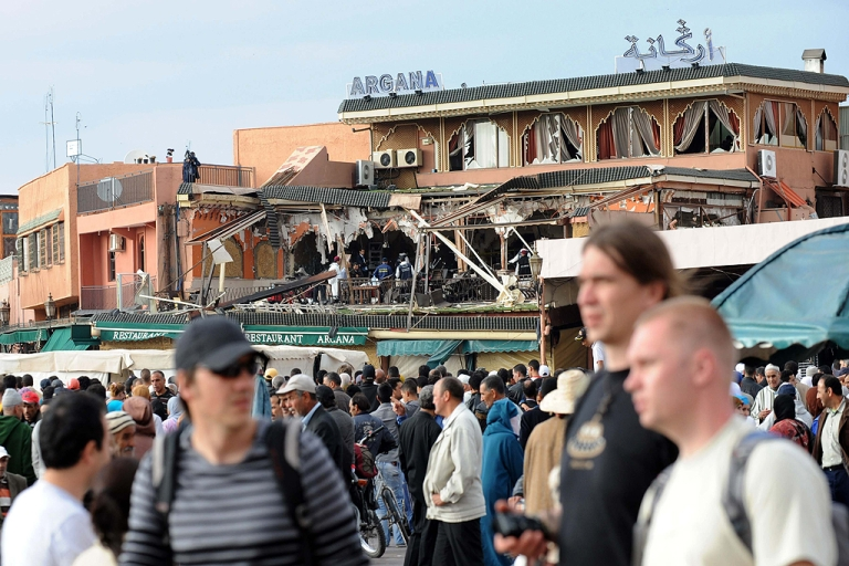 <p>Tourists walk past the cordonned-off area around the Argana restaurant (in background) in Jamaa El-Fna square in Marrakech is pictured on April 28, 2011 after a powerful blast killed 15 people there, six of them French nationals, public television reported quoting medical officials. An interior ministry official confirmed the report and said an investigation was under way to shed more light on the blast which occurred on Jamaa El Fna square, a favourite spot for foreign visitors, in central Marrakesh. Earlier reports spoke of the accidental explosion of several gas canisters in the Argana cafe in the middle of the square.</p>