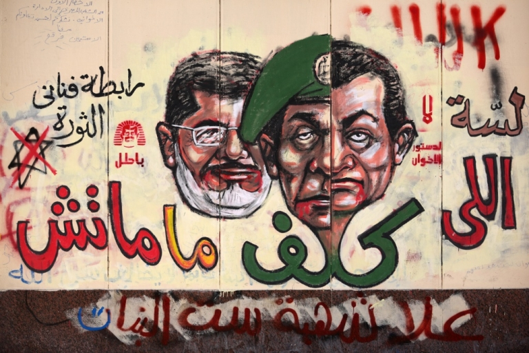 <p>Graffiti depicting Egyptian President Mohamed Morsi (L), ousted president Hosni Mubarak (R) and former head of the army Field Marshal Mohammed Hussein Tantawi cover the walls outside the presidential palace in Cairo.</p>
