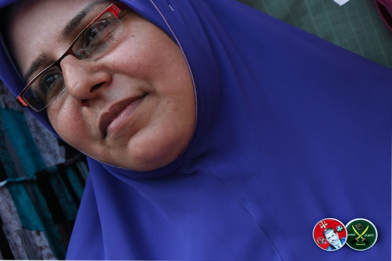 <p>An Egyptian woman wears a pin bearing the picture of Muslim Brotherhood presidential candidate Mohamed Morsi and another showing the logo of the party as thousands gather in Cairo's landmark Tahrir Square on June 22, 2012.</p>