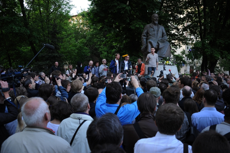 <p>Opposition activists listen to one of their leaders, Ilya Yashin (back L), during a rally at their camp in the Chistye Prudy district in central of Moscow, on May 15, 2012. The hundreds of opposition supporters who staged a week-long sit-in protest in central Moscow against Putin's rule were dispersed by police on the morning of May 16, 2012.</p>