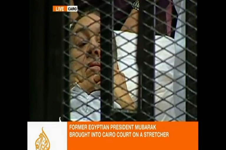 <p>This image taken from an Al Jazeera English video shows Hosni Mubarak lying on a hospital bed inside a cage in a courtroom in Cairo on Wednesday.</p>