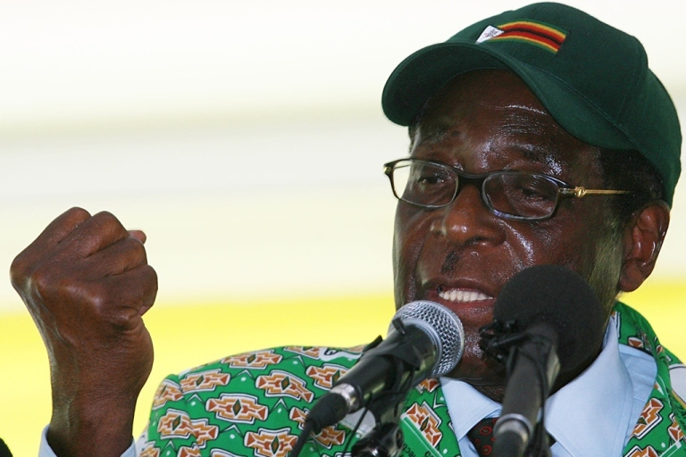 <p>Zimbabwe's President Robert Mugabe gives his trademark clenched fist salute as he speaks to officials of his Zanu-PF party on December 17, 2010. Mugabe said if America and Britain maintain sanctions on Zimbabwe his party will advocate for revenge and a takeover companies owned by western nationals</p>