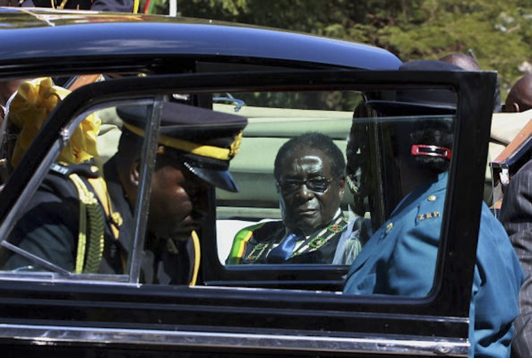 <p>Zimbabwe's President Robert Mugabe arrives in his motorcade for the opening of the third session of the parliament in Harare on July 13, 2010.</p>