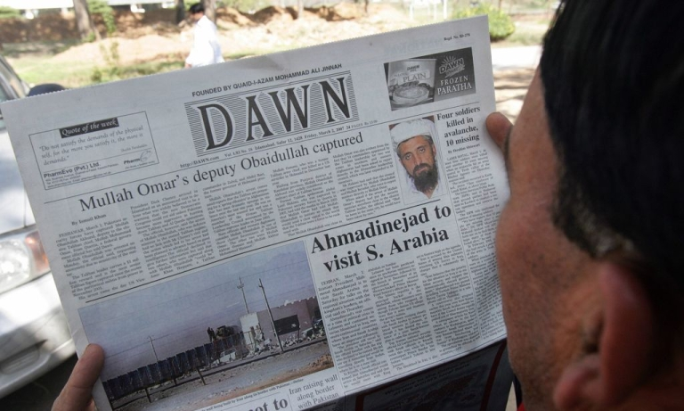 <p>A Pakistani man reads a newspaper with headlines about the arrest of top Taliban leader Mullah Obaidullah Akhund and his picture in Islamabad, 2 March 2007.</p>
