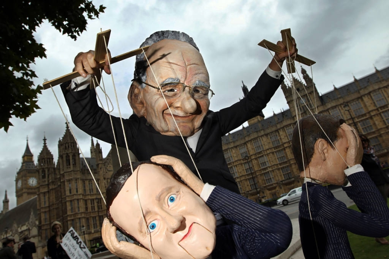 <p>A demonstrator dressed in a Rupert Murdoch mask controlled puppets of British Prime Minister David Cameron and British Minister for Culture, Media and Sport Jeremy Hunt, during a protest against Murdoch and Cameron's links to the News of the World phone hacking scandal.</p>