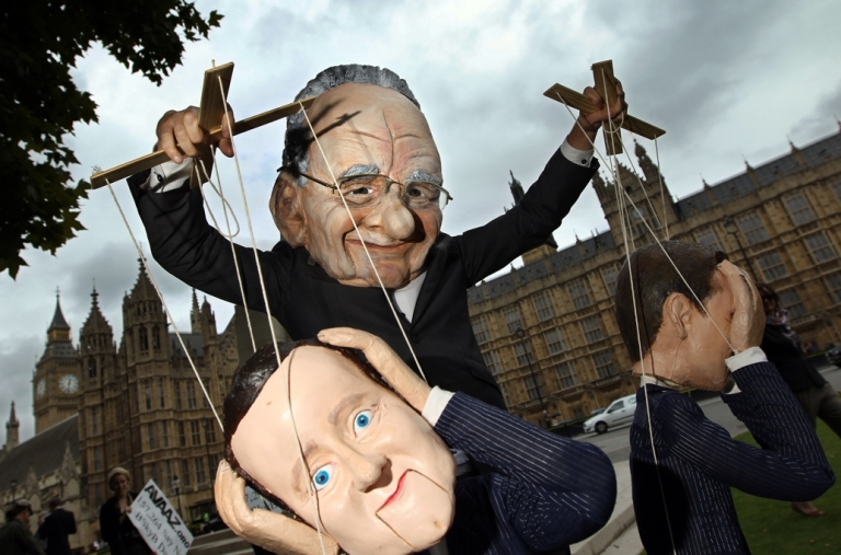 <p>A Rupert Murdoch puppet pulls the strings of British Prime Minister David Cameron (foreground) and Jeremy Hunt, the British minister for culture, media and sport.</p>
