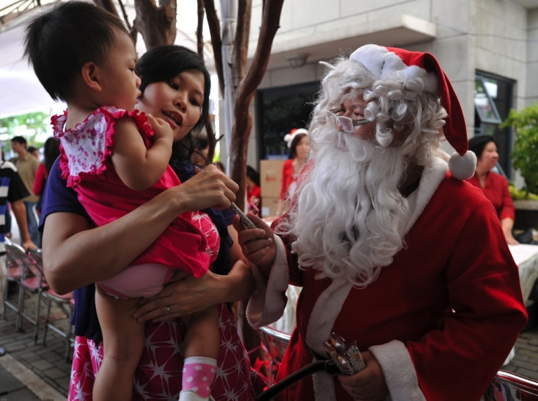 <p>An Indonesian child receives candy from a man dressed as Santa Claus in Jakarta on December 25, 2011.</p>