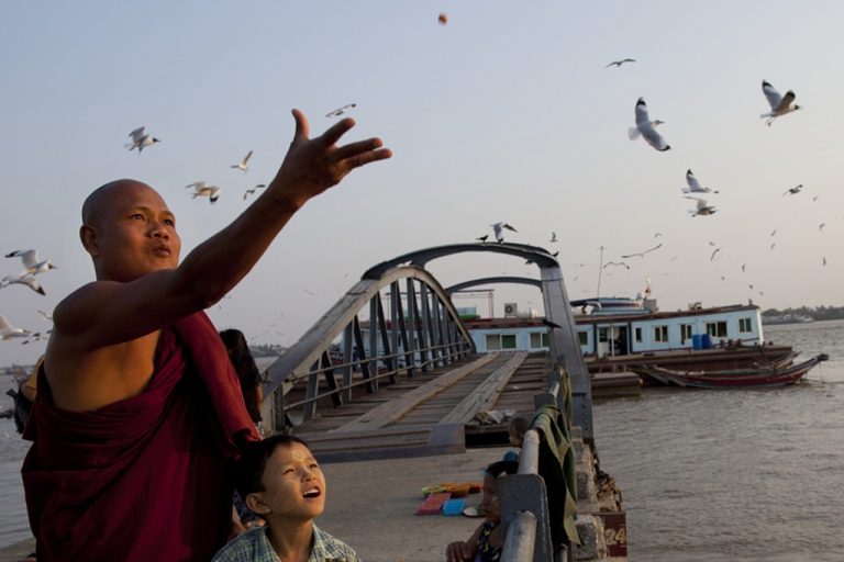 <p>A Burmese monk and his son feed the seagulls along the Yangon river ahead of the parliamentary elections March 29, 2012, Myanmar.</p>