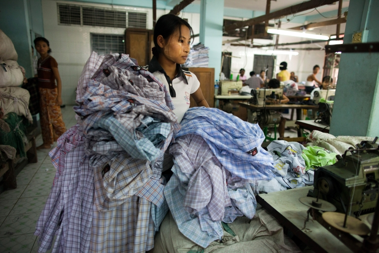 <p>A factory worker in Myanmar carries shirts at the TNT garment factory in Yangon, Dec. 9, 2011.</p>