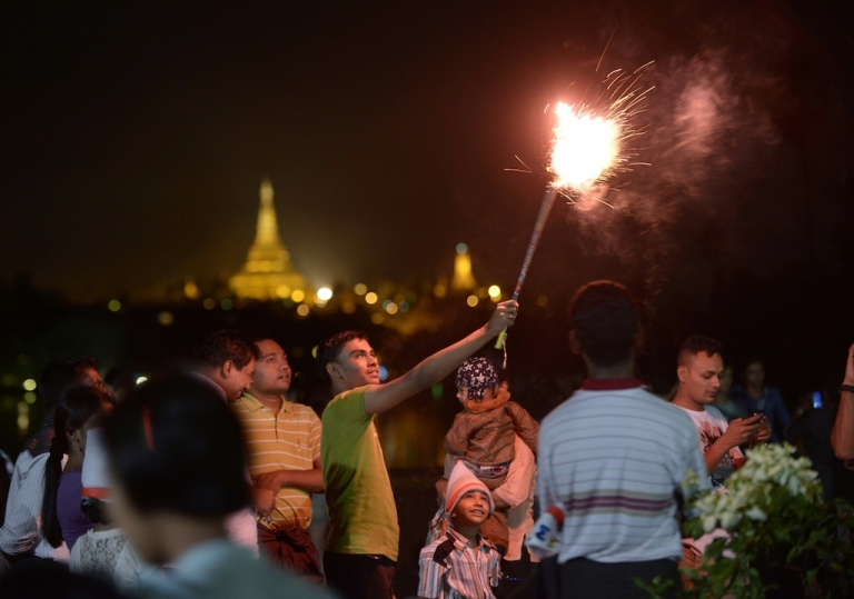 <p>People wait before the countdown to the New Year near the Shwe Da Gon pagoda and Kandawgyi Lake in Yangon on December 31, 2012. Some 50,000 people were expected to gather at the revered golden Shwedagon Pagoda in Yangon for the city's first public countdown to the New Year and fireworks.</p>