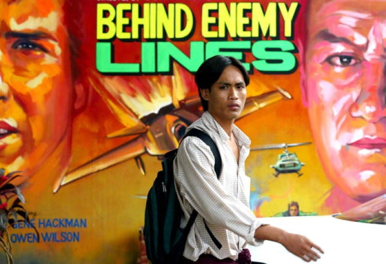 <p>YANGON, MYANMAR: A Burmese student walks past a large, hand-painted poster featuring the latest film from America in 2002.</p>