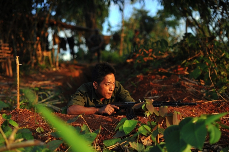 <p>A soldier from the All Burma Students Democratic Front - Northern Burma, an ally of the Kachin Independence Army, holding his weapon in September, 2012, as he looks out from an outpost near Laiza. (AFP PHOTO/ Soe Than WIN)</p>