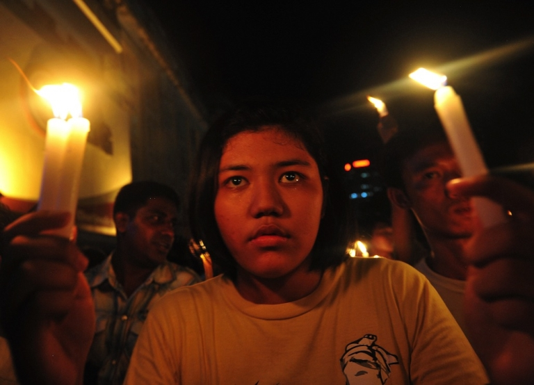 <p>Demonstrators in Myanmar walk with lit candles in a protest against severe power cuts in Yangon on May 23, 2012.</p>