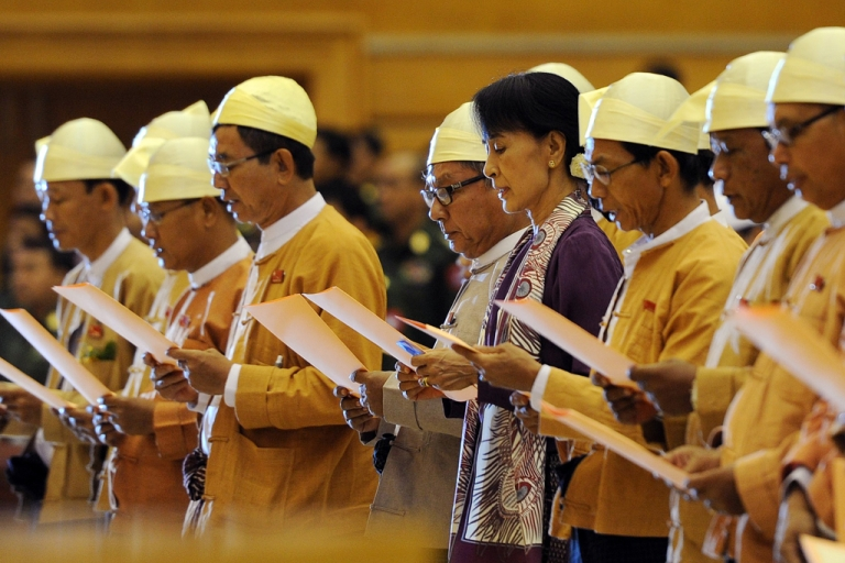 <p>Myanmar opposition leader Aung San Suu Kyi along with other elected members of parliament reads her parliamentary oath at the lower house of parliament during a session in Naypyidaw on May 2, 2012.</p>