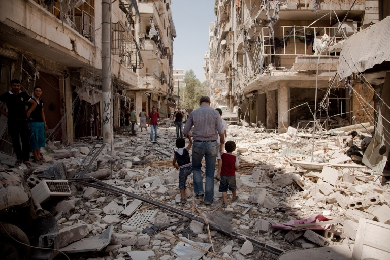 <p>A father walks with his children through the rubble after a war plane bombed the Salahadin neighborhood of Aleppo, Syria, on Aug. 1, 2012. Few civilians remain in the district and those who stay face heavy shelling from tanks, fighter jets, helicopters and rockets.</p>