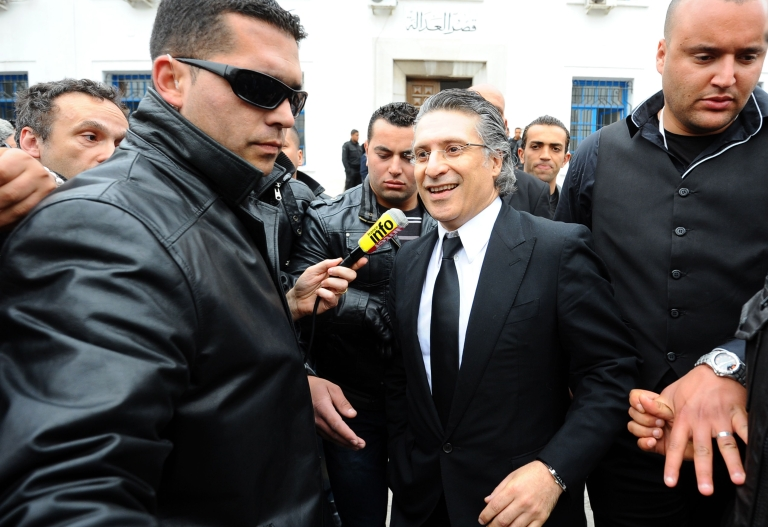 <p>The director of the Tunisian TV channel Nessma, Nabil Karoui (C), leaves a Tunis courthouse on April 19, 2012.</p>