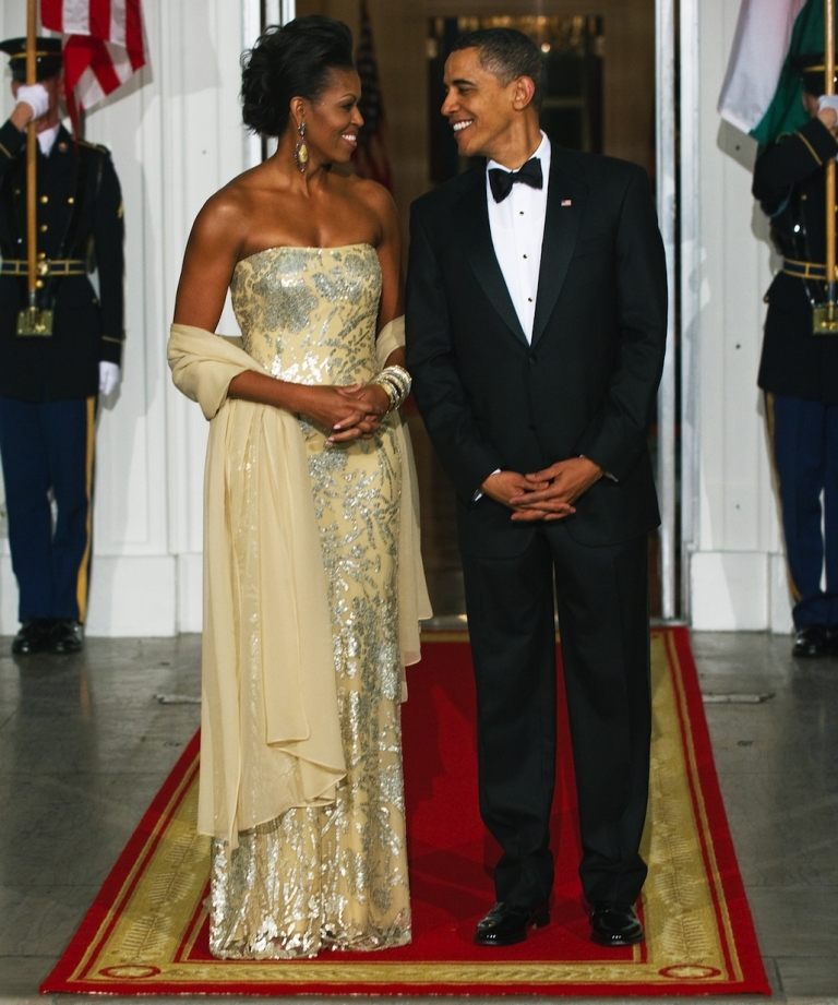 <p>US President Barack Obama stands with First Lady Michelle Obama shortly before greeting Indian President Manmohan Singh and his wife Gursharan Kaur at the North Portico of the White House November 24, 2009, as the Obamas hosted their first official State Dinner. Mrs. Obama wore a gold dress by Indian-American designer Naeem Khan.</p>