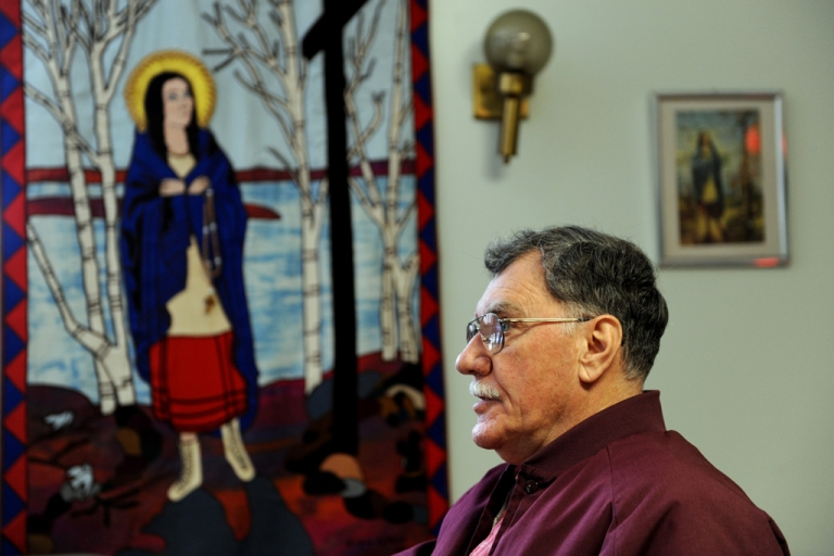 <p>Friar Mark Steed speaks in front of a tapestry of Kateri Tekakwitha, a 17th-century Mohawk woman who the Vatican will canonize Oct. 21, at the National Kateri Shrine in Fonda, NY. Kateri will become the first Native American saint.</p>