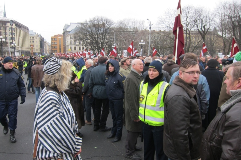 <p>Monica Lowenberg, whose uncle was murdered in Riga by the Nazis, watches annual parade honoring Latvian Legion of the Waffen-SS (photo courtesty of DefendingHistory.com)</p>