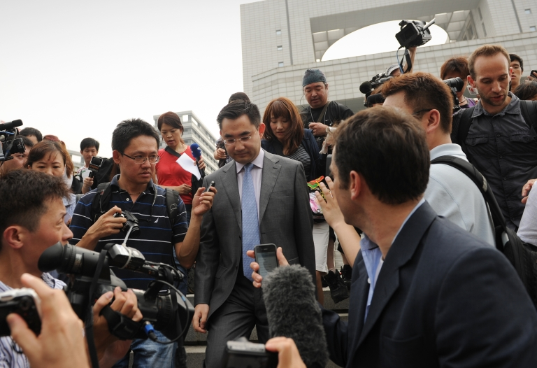 <p>Reporters surround He Zhengsheng, a lawyer for Neil Heywood's family, as he leaves the Intermediate People's Court in Hefei, Anhui, China, on Aug. 20, 2012.</p>