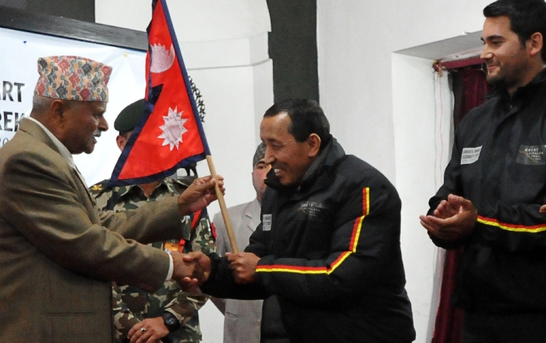 <p>Nepal's President Ram Baran Yadav (L) hands over the country's national flag to Nepalese climber Apa Sherpa (2R) who holds the record for the number of times he has summitted Mount Everest, flanked by his team members at the President's Office in Kathmandu on January 12, 2012. On January 15, Apa and his team will begin their trek on the 1700 kilometre, 120 days trek dubbed 'Great Himalayan Trail' to highlight the impacts of climate change.</p>