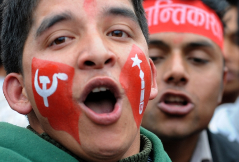 <p>Unified Communist Party of Nepal (Maoist) chairman Pushpa Kamal Dahal known as Prachanda waves to the crowd during a mass meeting organised by Maoists to mark the 17th anniversary of the start of their