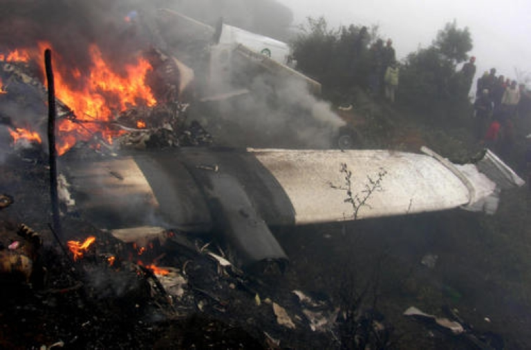<p>In this picture taken on October 9, 2008, bystanders look on as the wreckage of a Yeti Airlines aircraft burns at the airport in Lukla.  Mistakes by the crew of a plane that crashed in Nepal's Everest region caused the accident which killed 18 people, officials said January 1, 2009, as a report into the accident was released. Fifteen people including 13 Indian tourists were killed when an aircraft with 21 people on board crashed at Jomsom airport in north-central Nepal on Monday morning.</p>