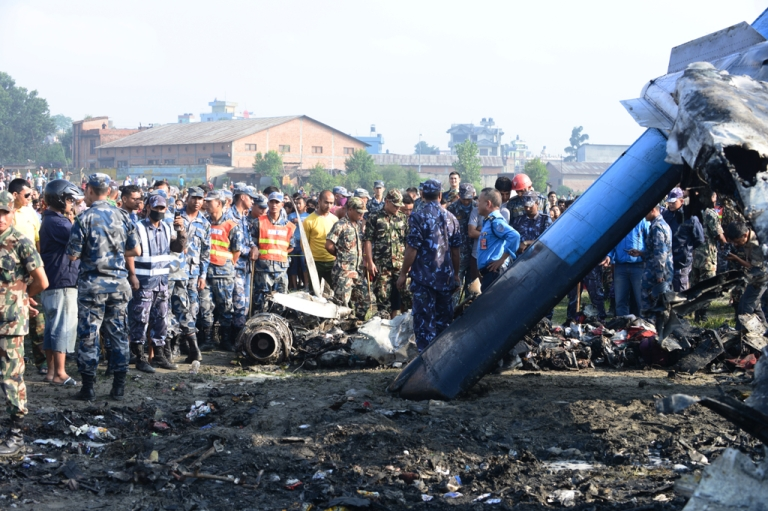 <p>Nepalese rescue team members looks at the remains of a Sita air plane after it crashed in Manohara, Bhaktapur on the outskirts of Kathmandu on September 28, 2012.</p>