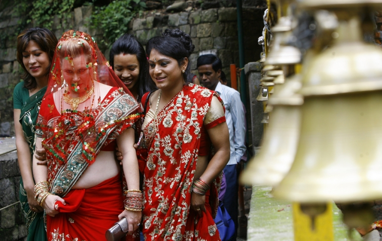 <p>US lesbian Sarah Welton (L) arrives for her wedding ceromony in a Hindu temple on the outskirts of Kathmandu on June 20, 2011.  The couple tied the knot in a Hindu ceremony at a temple in Nepal, becoming the first same-sex couple to so in a public function. Courtney Mitchell, 41 and Sarah Welton, 48, both from Denver, Colorado in the United States, exchanged garlands as a Hindu priest chanted mantras and Nepalese artisans played traditional musical instruments in a temple complex 22 kilometres (13 miles) south of Kathmandu.</p>