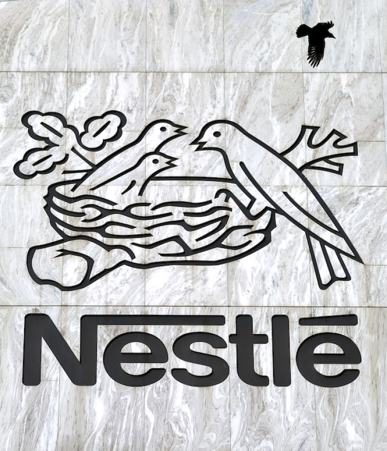 <p>A crow flies above a Nestle sign at the company's headquarters in Vevey, Switzerland.</p>