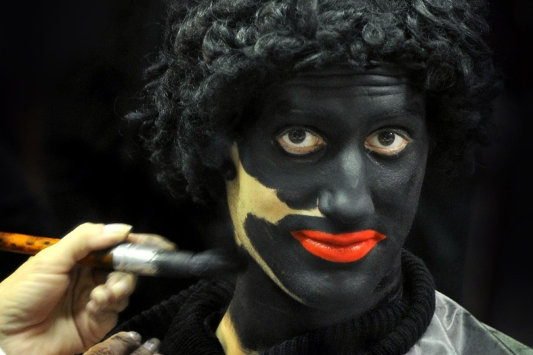<p>A person applies makeup on a man dressed as Black Peter prior to a celebration in a primary school, on December 3, 2010 in Soest, Netherlands.</p>