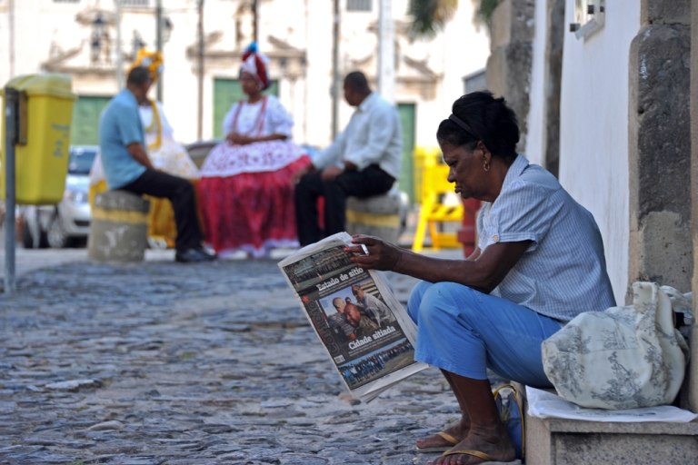 <p>A woman reads a newspaper in Salvador, Bahia, Brazil.</p>