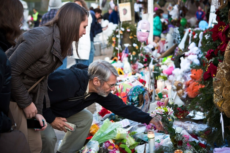 <p>A man lays flowers at a memorial on December 24, 2012 for those killed in the shooting at Sandy Hook Elementary School in Newtown, Connecticut.</p>