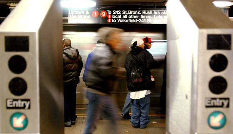 <p>A man was arrested with two loaded guns in a Manhattan subway Sunday night, after a police officer noticed him trying to go through a turnstile without paying.</p>