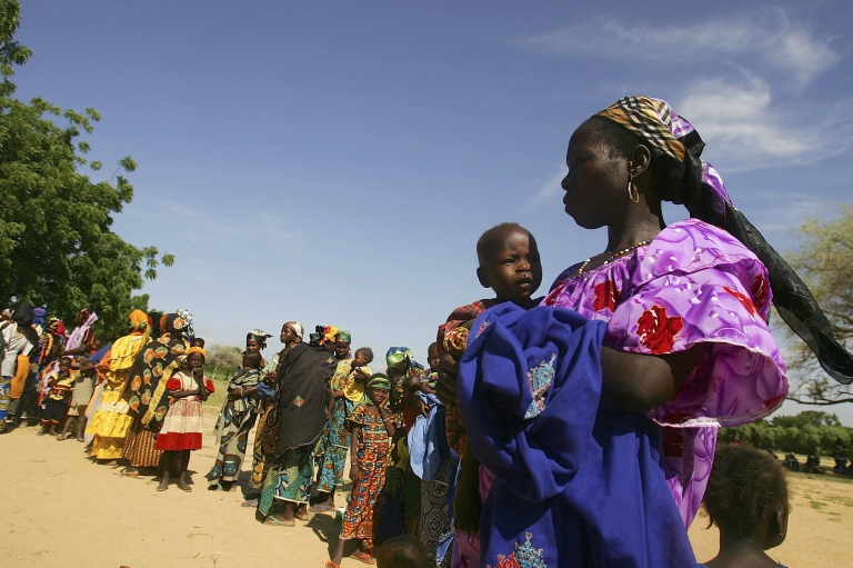<p>TESSAOUA, NIGER:  Hundreds of women in Niger wait in line with their malnourished children to receive aid from the Save The Children Clinic on August 10, 2005.   A combination of severe drought and a locust plague caused that famine, which affected at least 2 million people in Niger alone.</p>